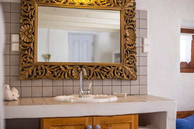 Einrichtungsdetail: Spülstein mit großem Spiegel im Badezimmer.