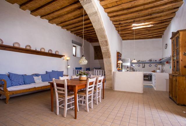 Turmhaus: Foto-Totale mit Rundbogen über Schlafempore, Eßtisch und Sitz-Divan. Blick in den Küchenbereich, rechts Geschirrschrank.