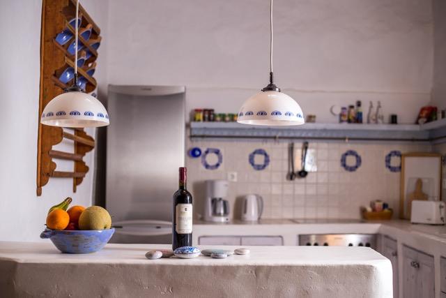 Detailansicht in den Küchenbereich mit Weinflasche auf Anrichte, Kühlschrank und Kochbereich.