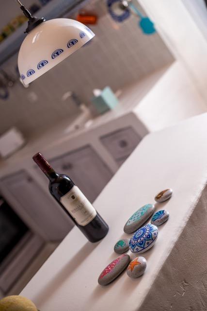 Detailansicht in den Küchenbereich mit Weinflasche auf Anrichte, Spülstein und Deckenleuchte..