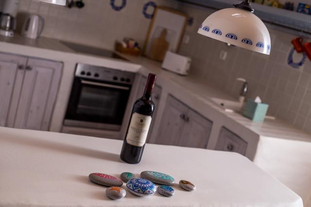 Detailansicht in den Küchenbereich mit Weinflasche auf Anrichte, Spülstein und Kochbereich.