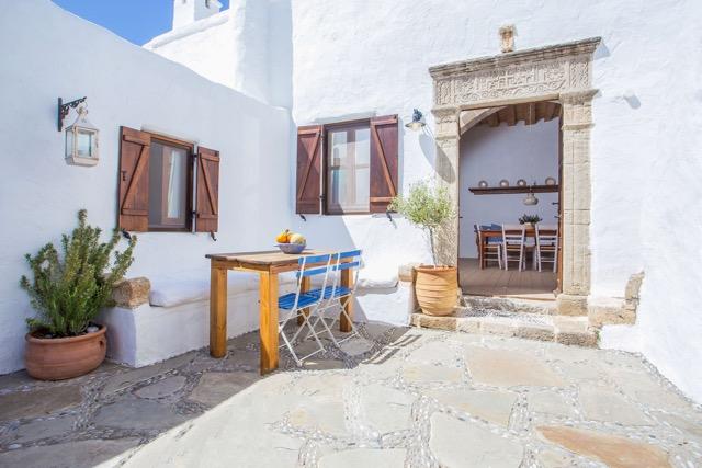 Foto Innenhof und Vespertisch mit Blick durch die Eingangstür in den Wohnbereich mit Eßtisch und Balkendecke