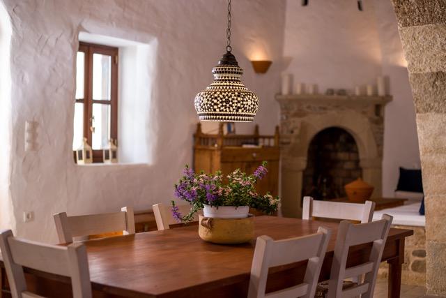 Eßtisch unter dem Rundbogen mit Blick auf Kamin, Sitzecke und Anrichte.