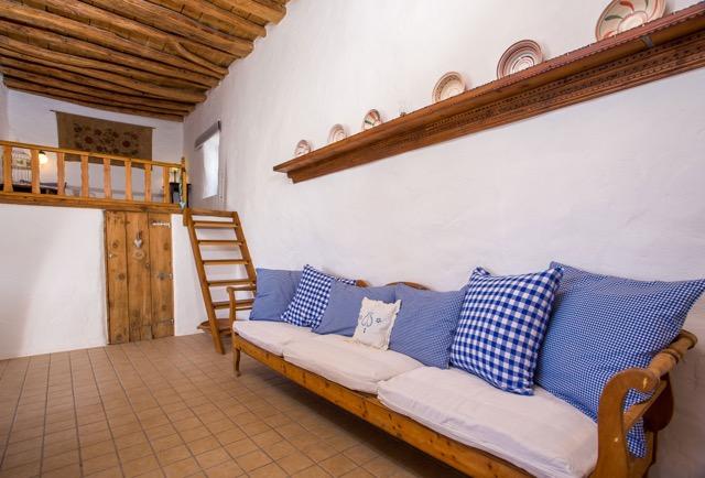 Wohn-Divan vor der Schlafempore mit Holzdecke und Stiegenleiter.